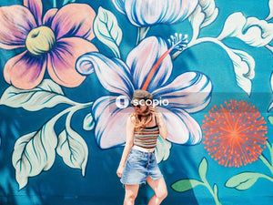 Woman in blue denim shorts standing beside blue and green floral wall