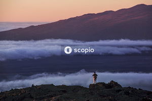 Person standing on rock formation near sea of clouds