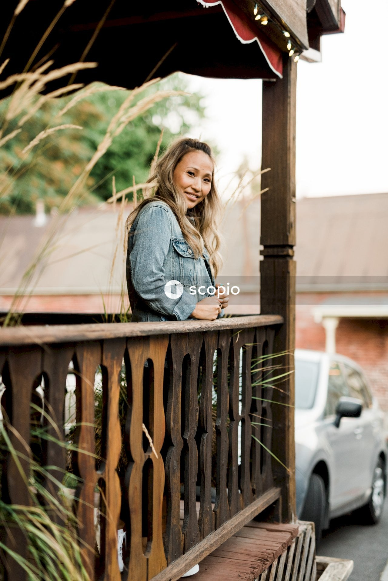 Woman in black long sleeve shirt standing beside brown wooden fence