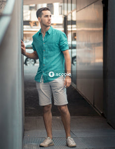 Man in blue polo shirt and white shorts standing beside glass wall