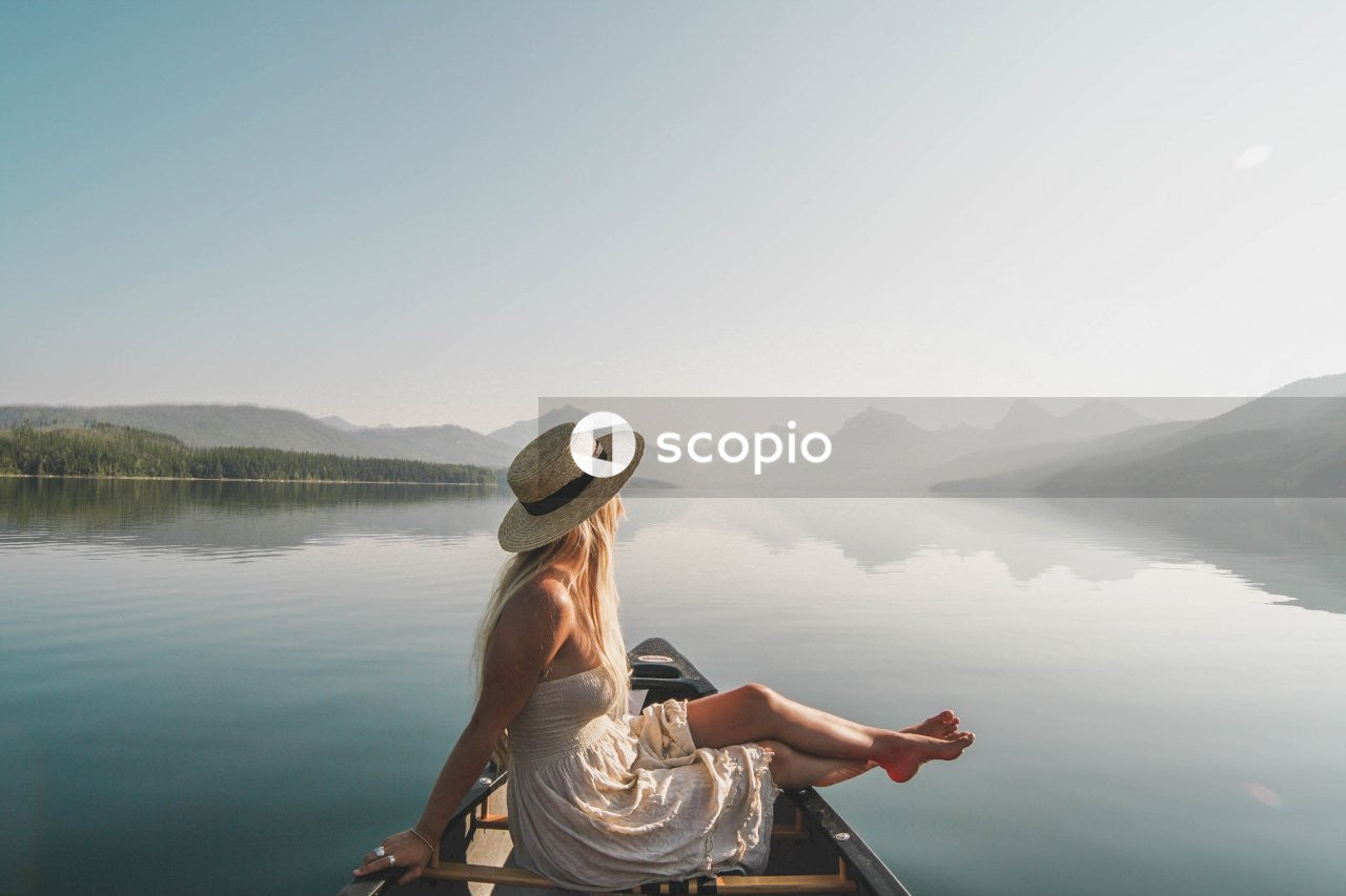 Woman in white tank top and brown hat sitting on boat