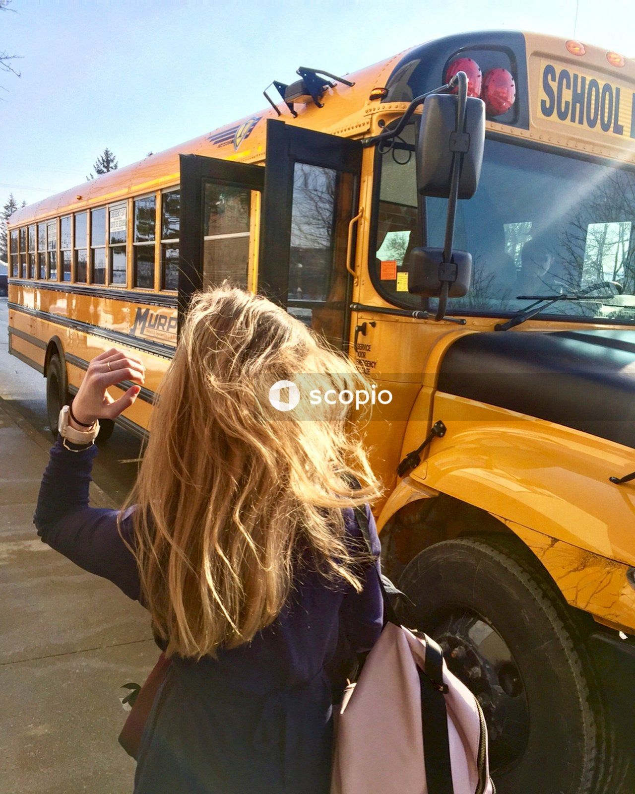 Woman in black jacket standing near yellow bus