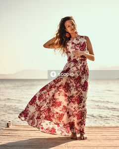 Woman in red and white floral sleeveless dress standing on beach