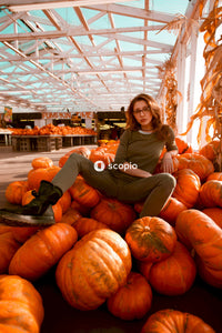 Woman in gray long sleeve shirt sitting on pumpkin