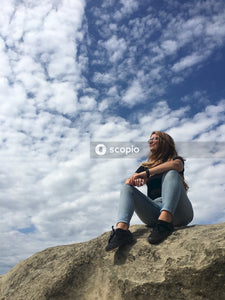 Woman in black long sleeve shirt and gray pants standing under white clouds
