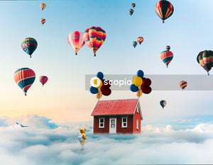 Assorted-colored hot air balloons pulling red wooden house on skies