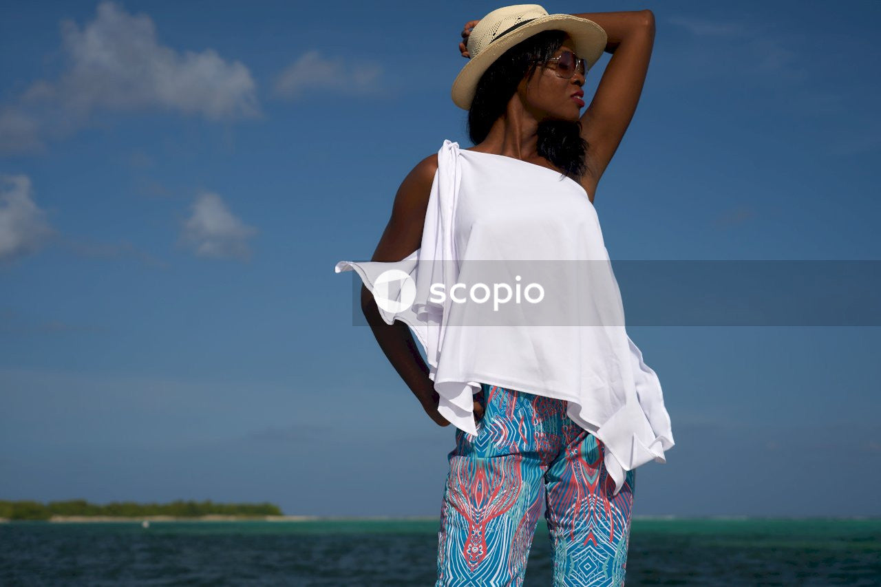 Woman in white shirt and blue and green floral pants wearing white sun hat standing on near near near near