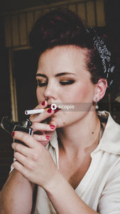 Woman in white collared shirt holding black disposable lighter