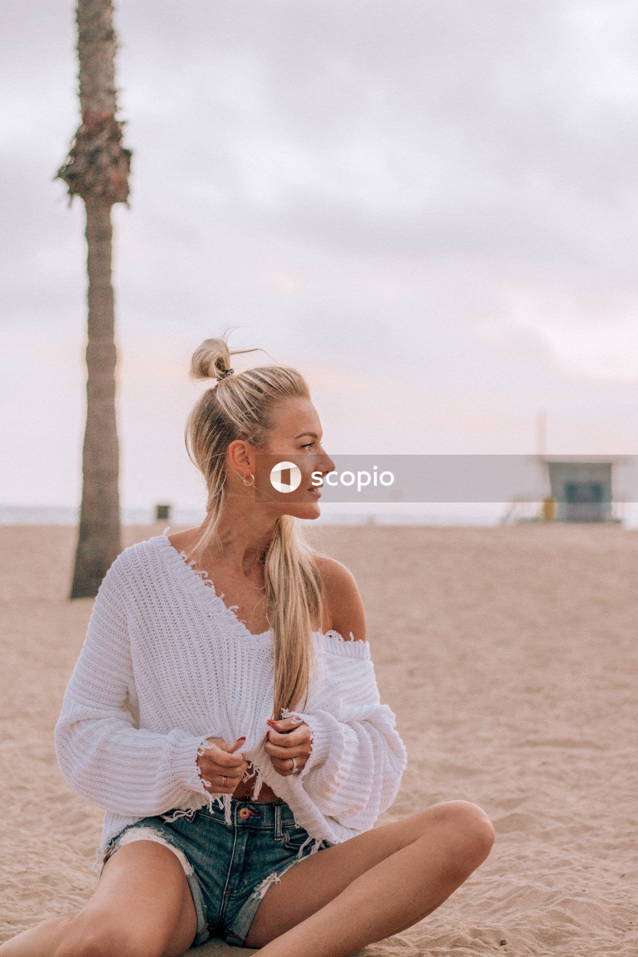 Woman in white knit sweater standing on beach