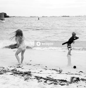 Grayscale photography of boy and man standing on shore