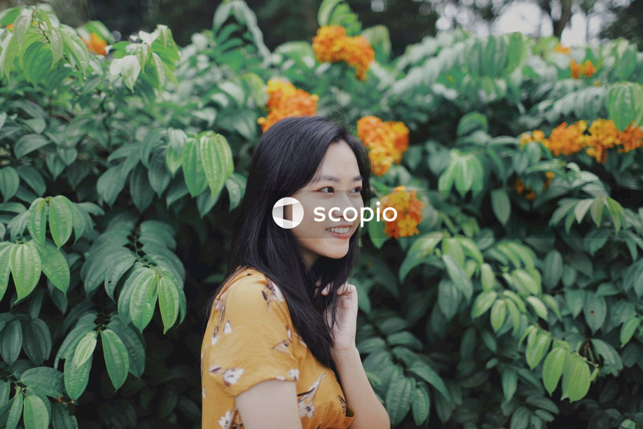 Woman in yellow floral dress standing near yellow flowers