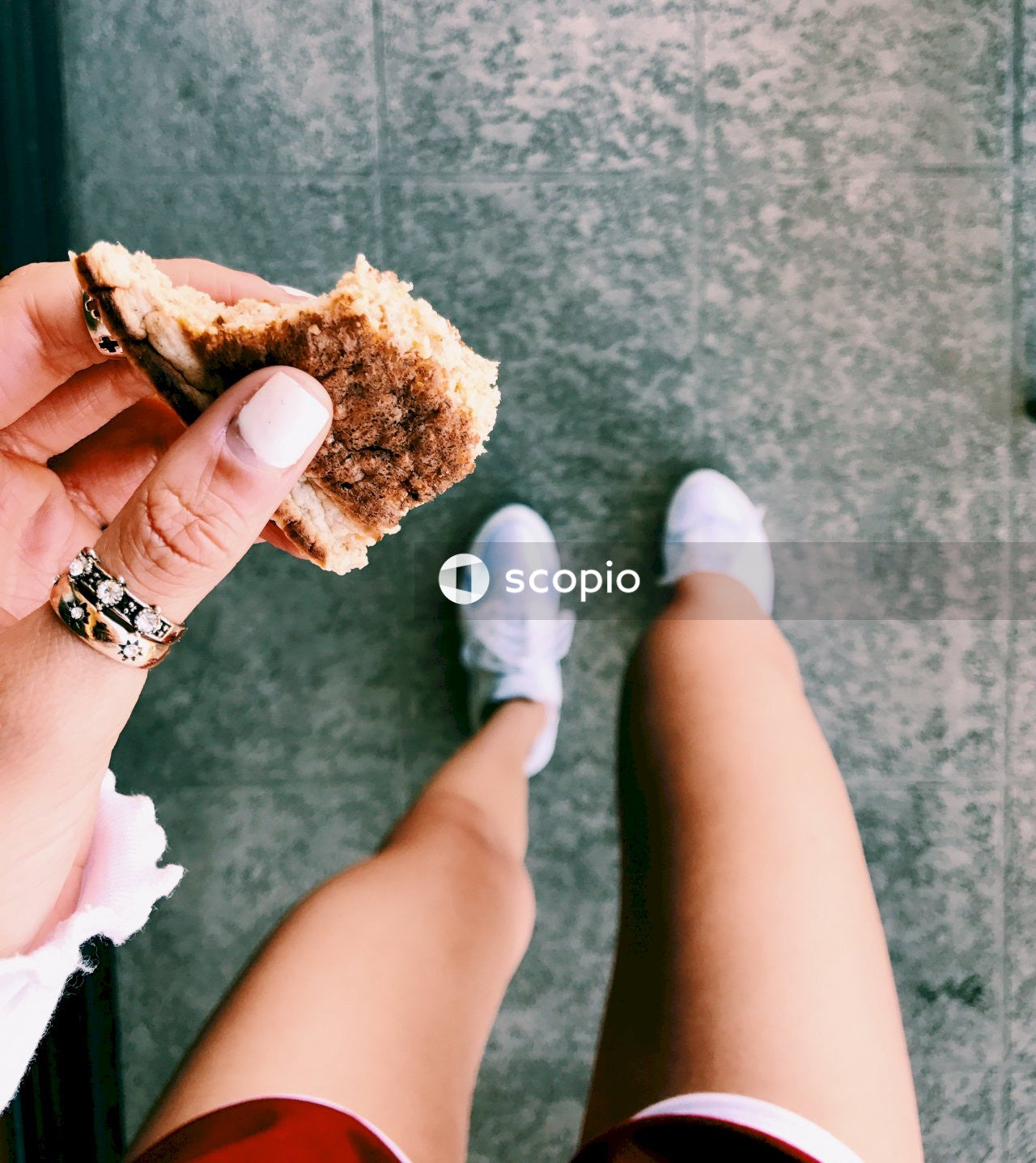 Person holding brown bread with white cream