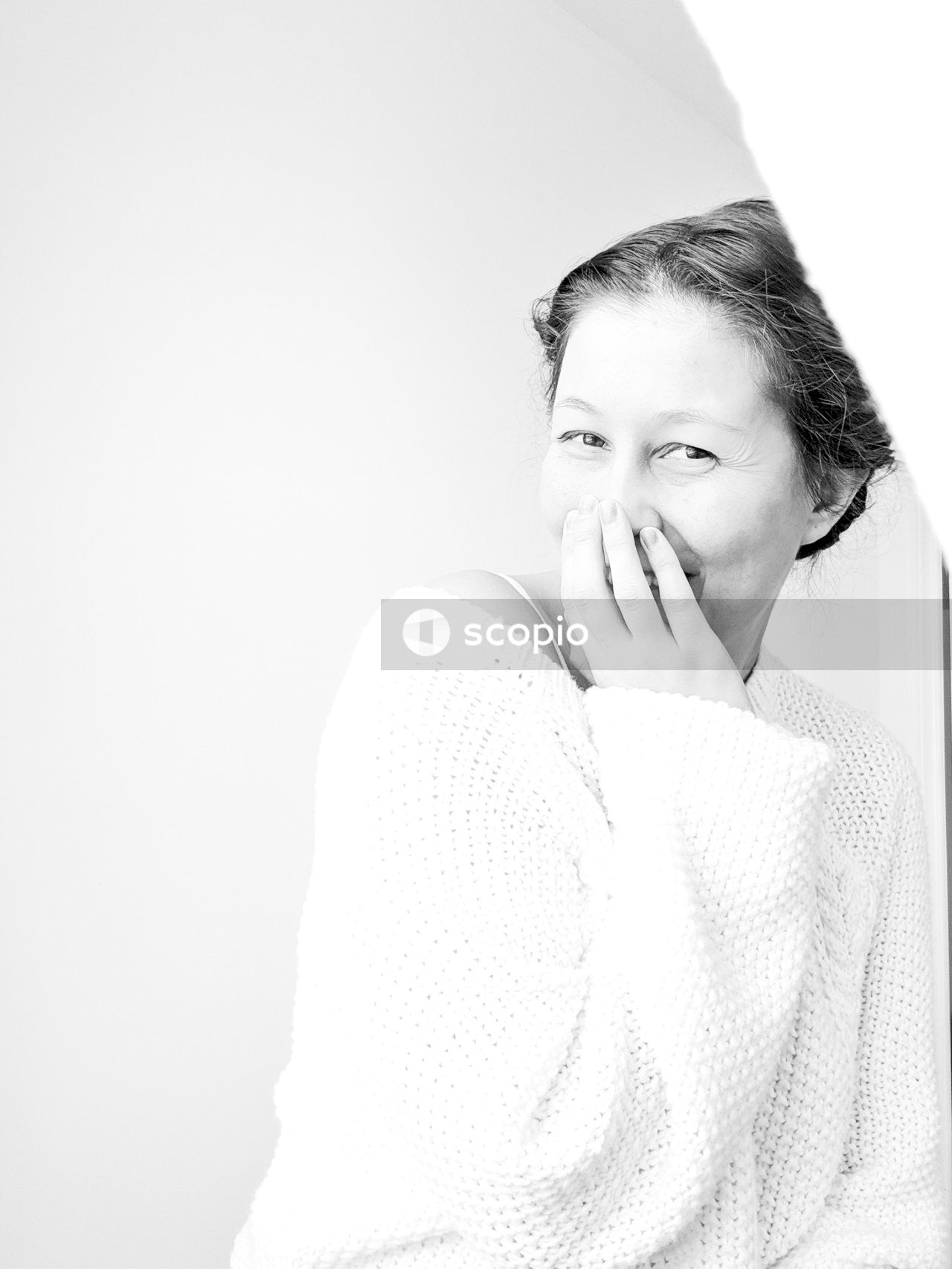 Woman smiling and covering her mouth with her hand