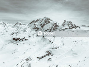 Utility towers and building on mountain covered with snow