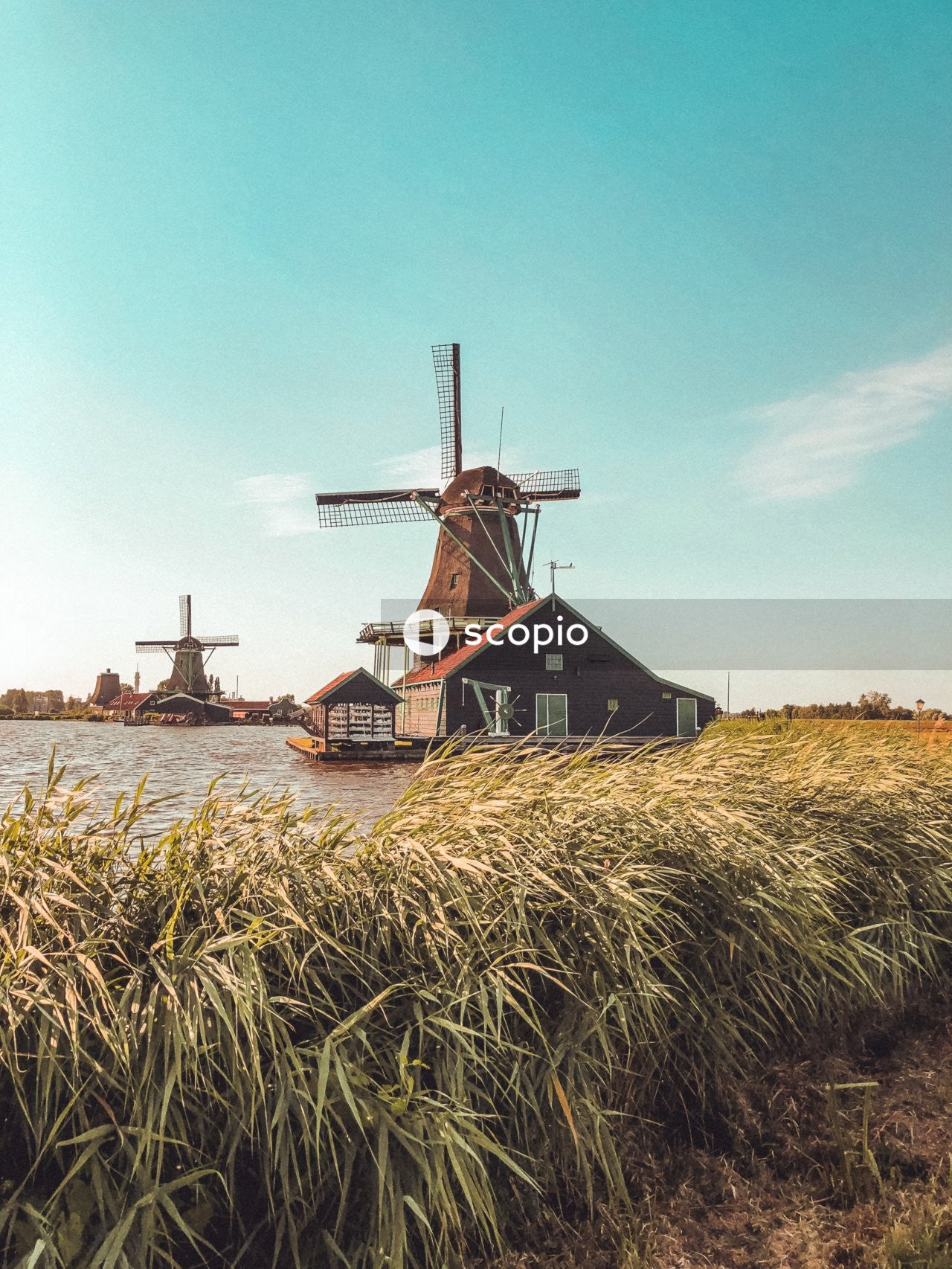 Brown windmill near body of water