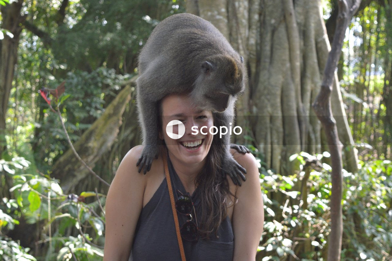 Woman in blue tank top carrying baby monkey