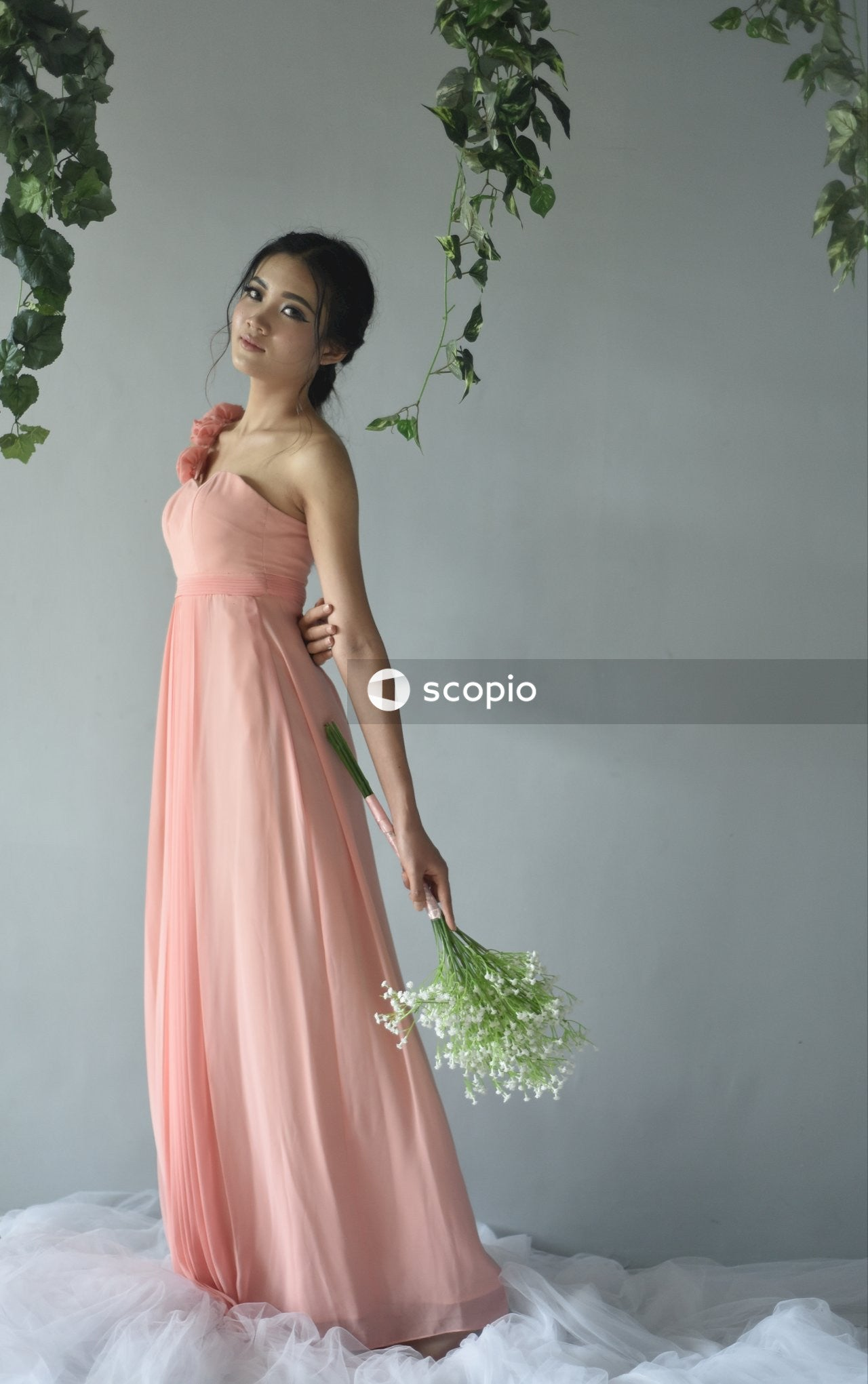 Woman in pink dress holding bouquet of flowers