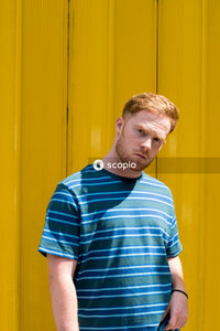 Man in blue and white striped crew neck t-shirt standing beside yellow wall