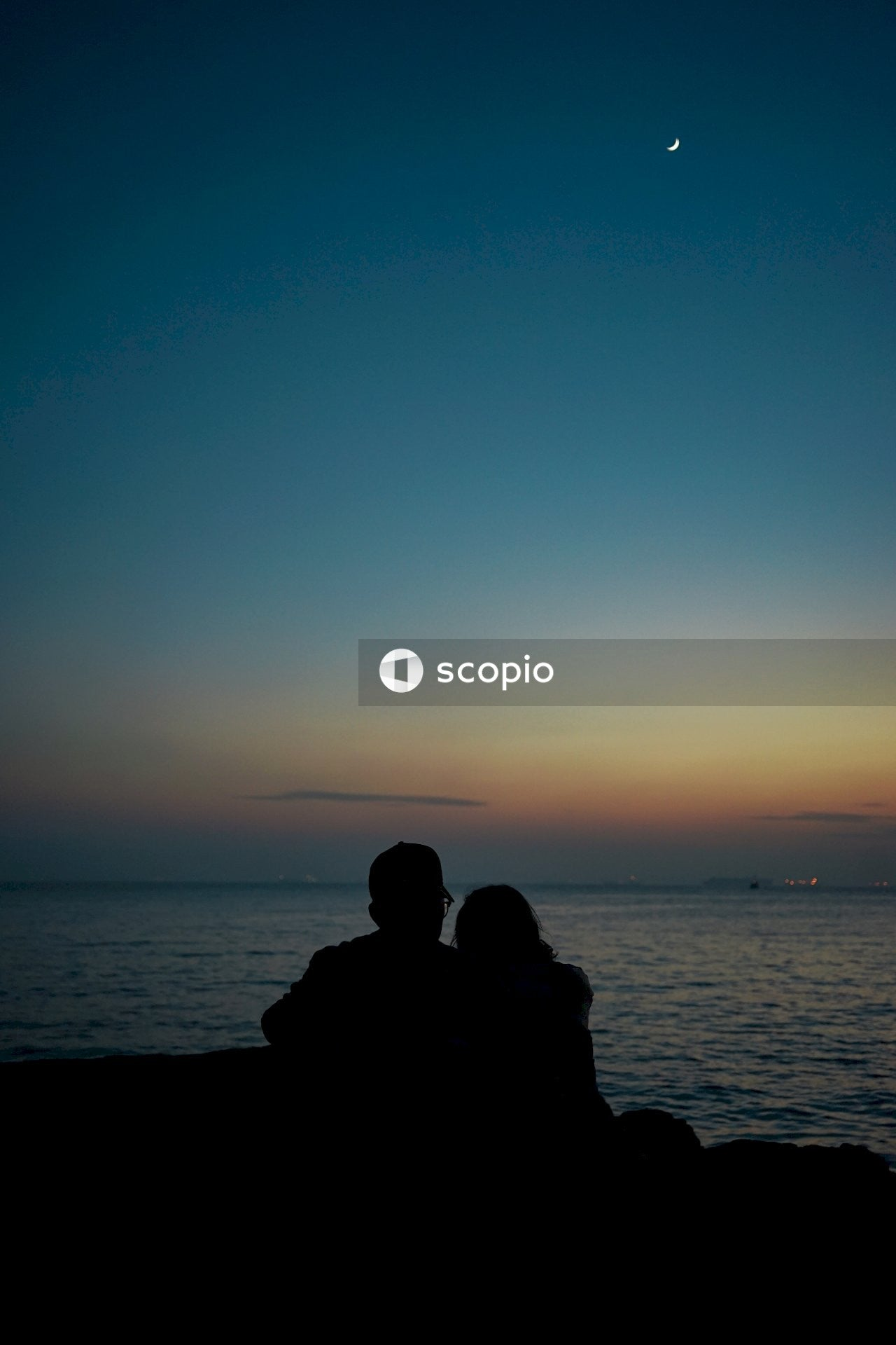 Silhouette of man and woman sitting beside ocean