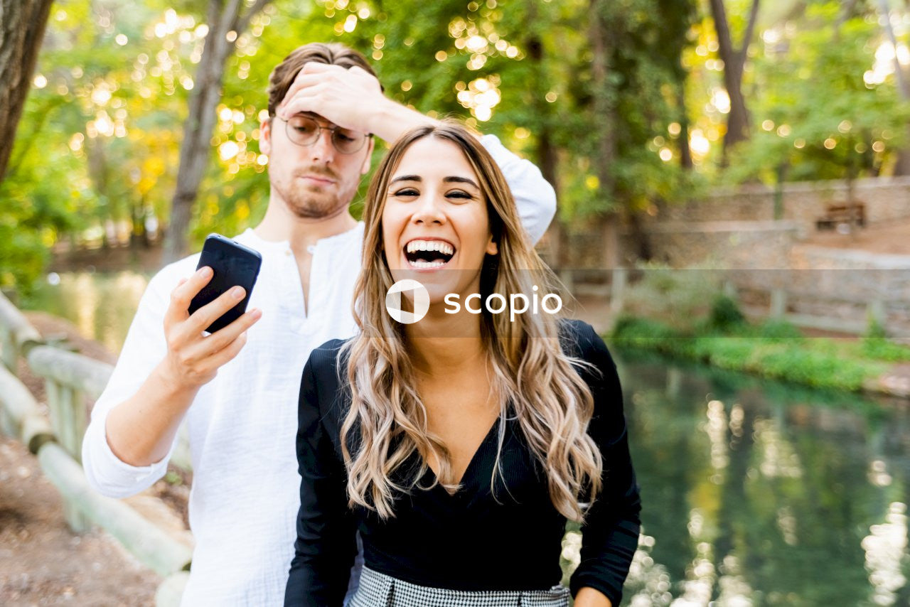 Smiling woman standing beside man using smartphone