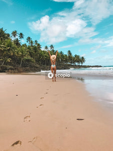 Woman in white bikini walking on beach
