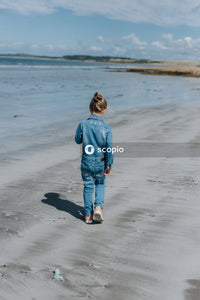 Girl in blue long sleeve shirt and blue denim jeans standing on beach
