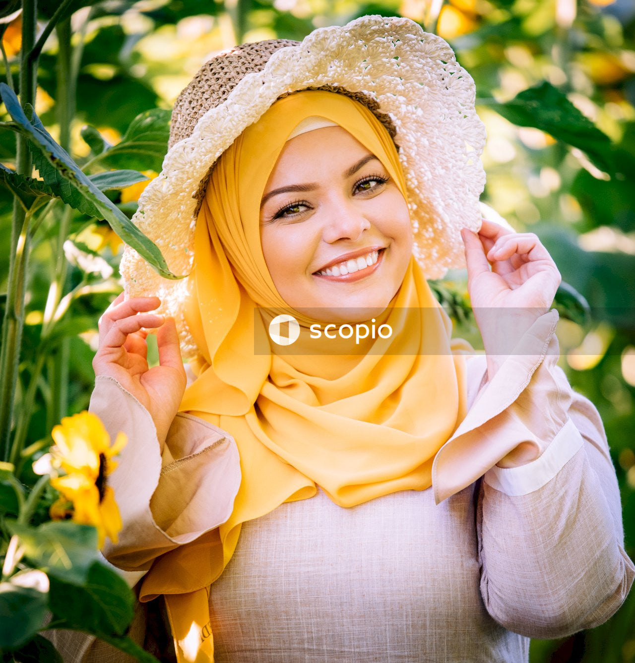 Woman in yellow hijab holding yellow flowers
