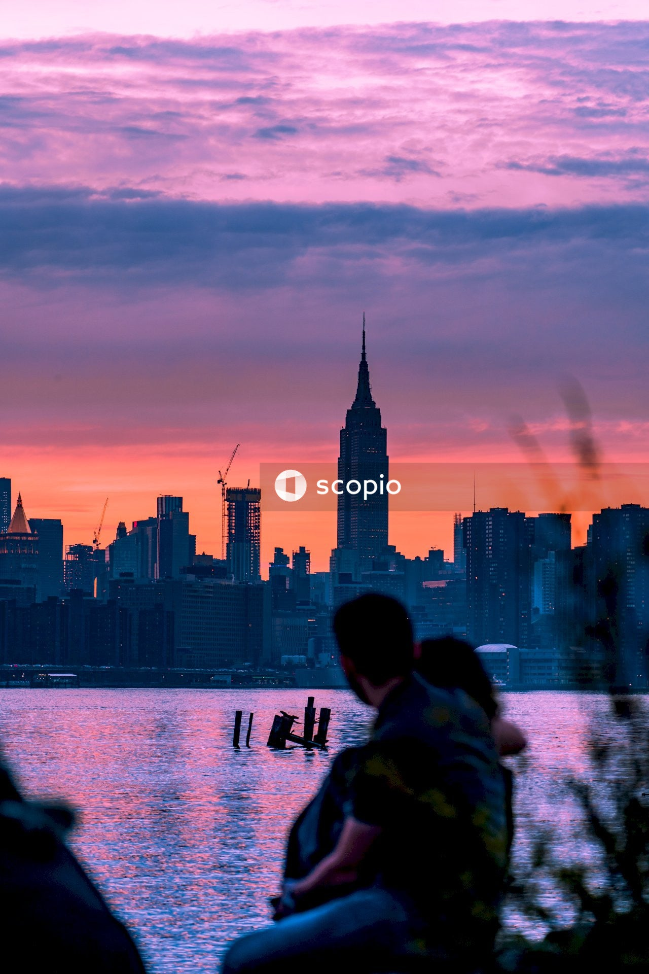 Man and woman sitting on bench looking at the city skyline