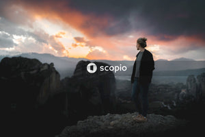 Man in black jacket standing on rocky mountain during sunset