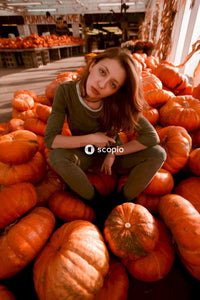 Girl in gray long sleeve shirt lying on orange pumpkins