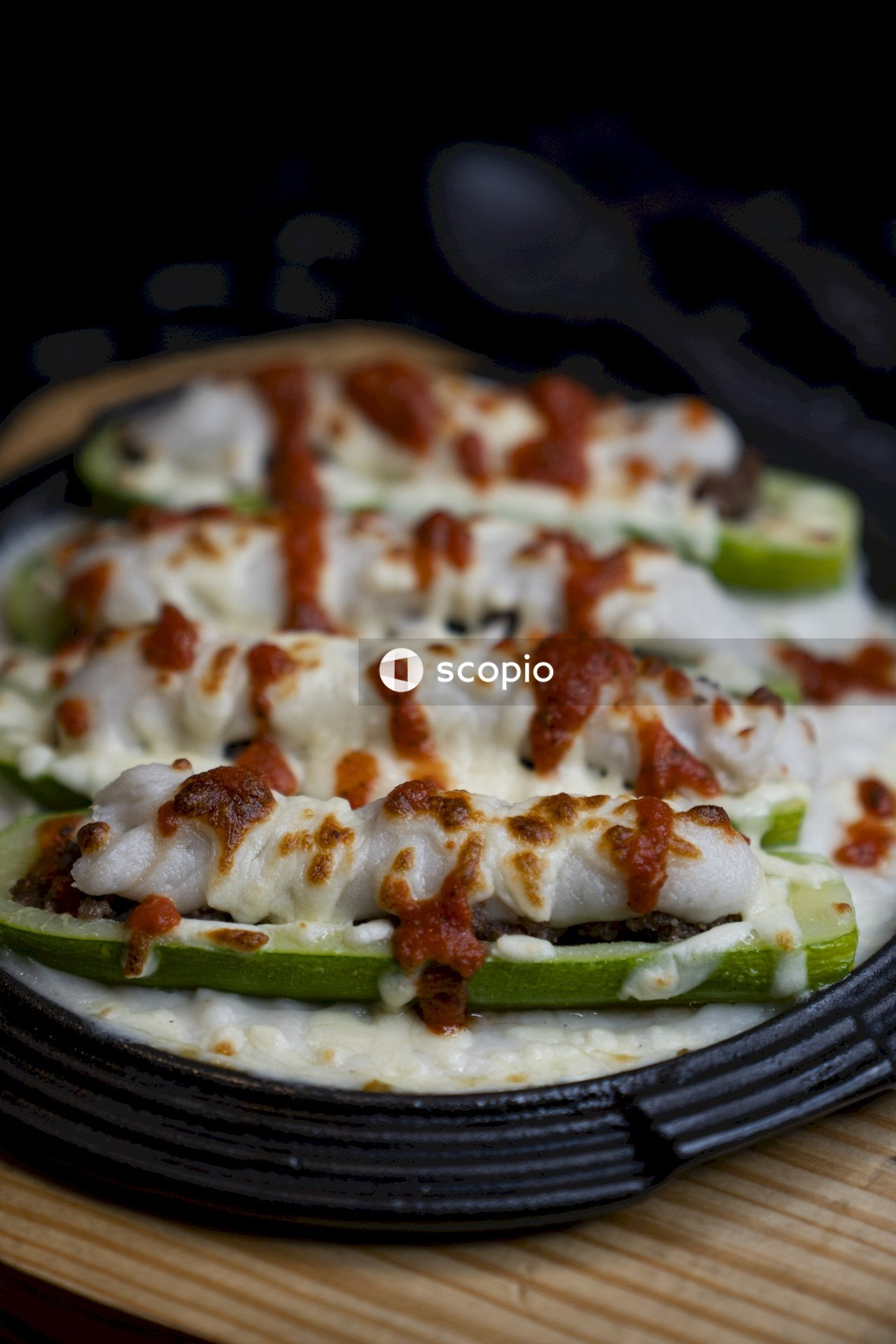 Pizza with white cream and green leaf on black plate