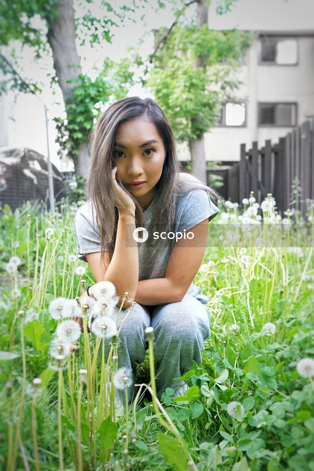 Woman in gray t-shirt sitting in front of white flowers