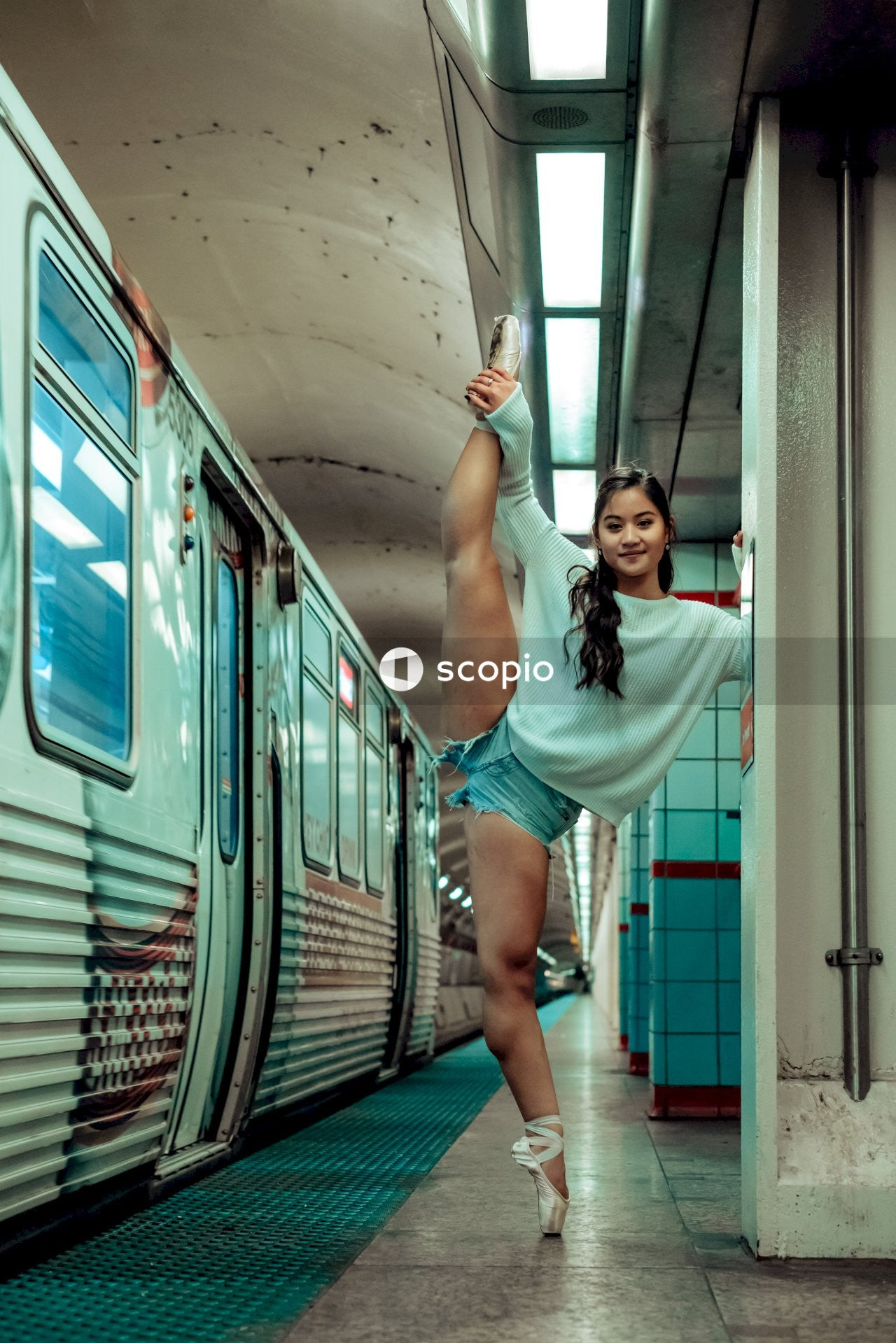 Young woman doing splits in subway station