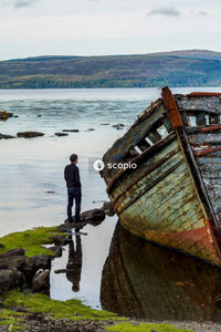 Man standing near abandoned boat viewing sea and mountain