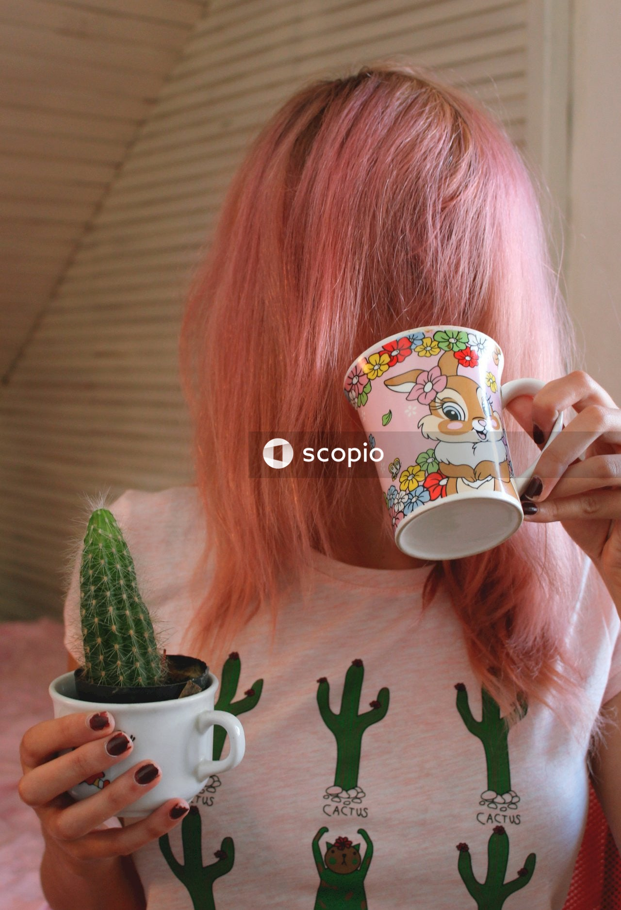 Woman with pink hair holding a mug and a cactus