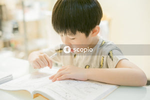 Aerial shot of boy writing in notebook