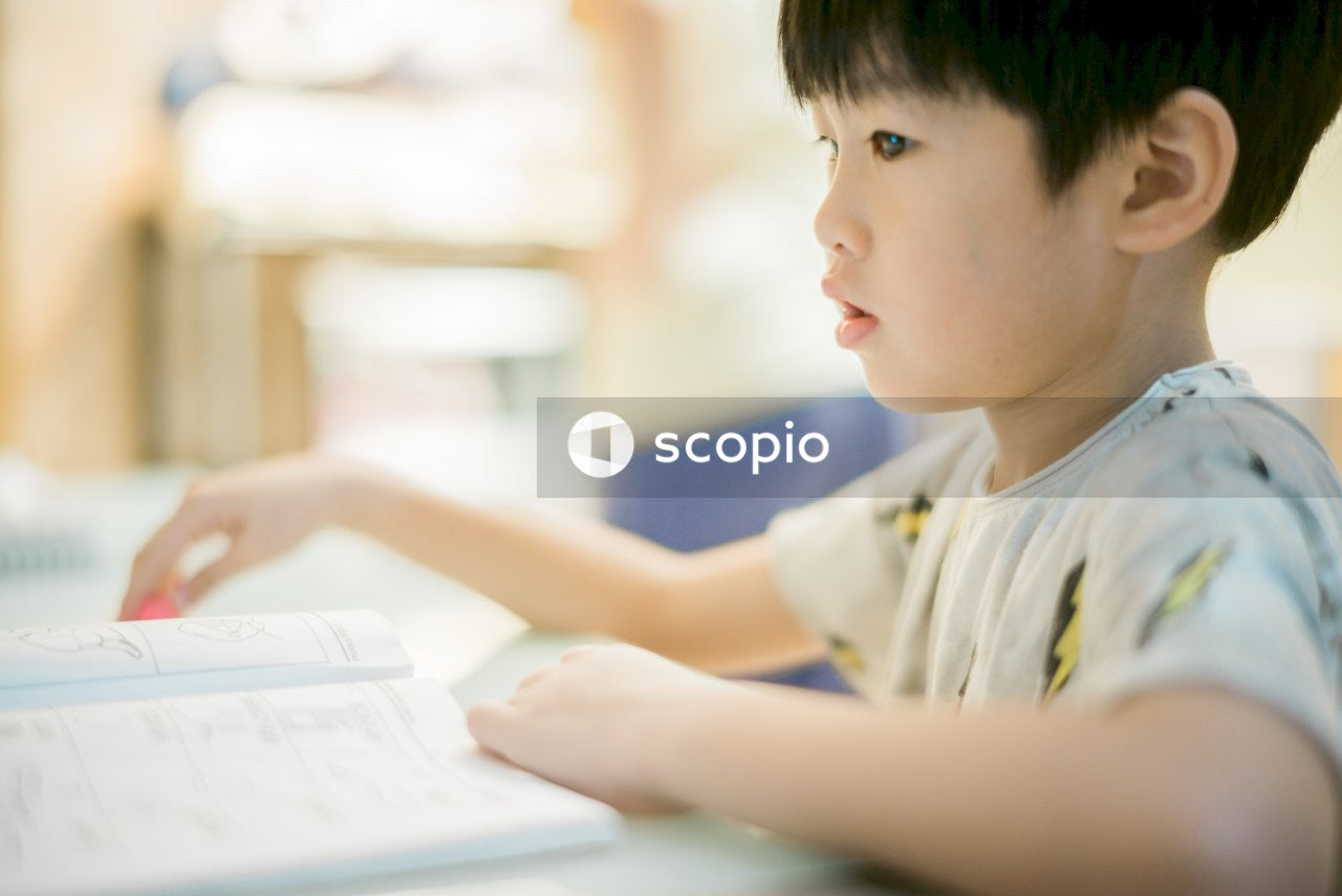 Young boy writing in notebook