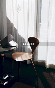 Brown wooden chair beside laptop on table
