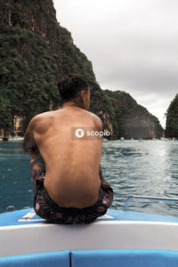 Topless man sitting on blue and white boat