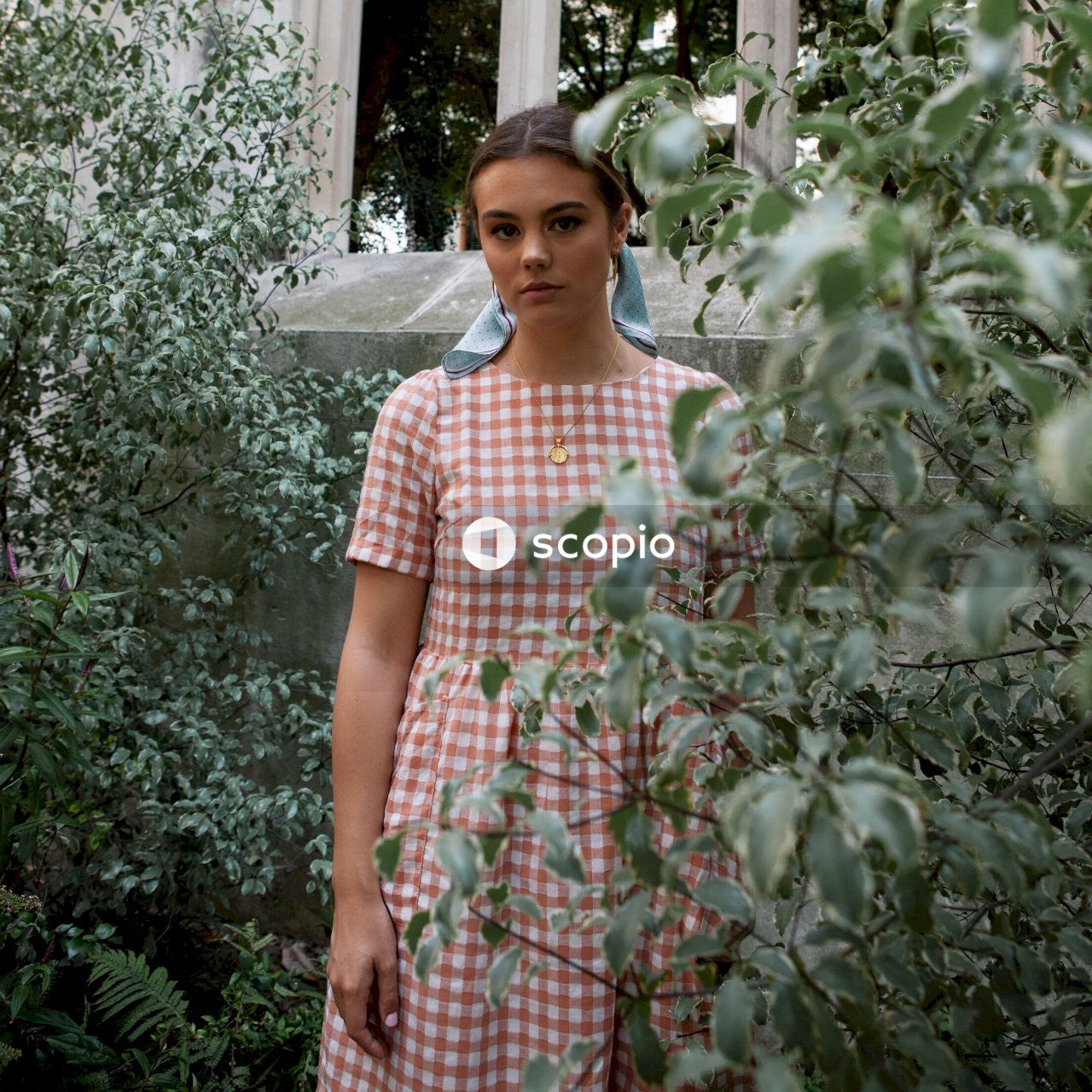Woman in white and pink plaid dress standing beside green plants
