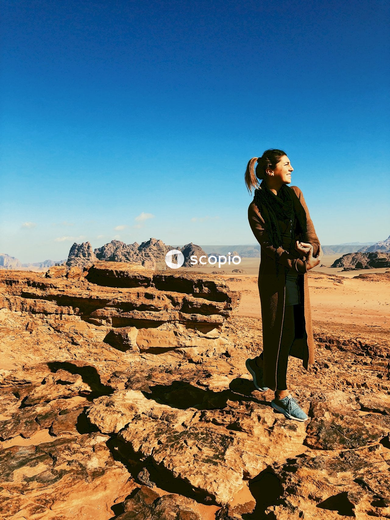 Woman in black coat standing on rocky hill