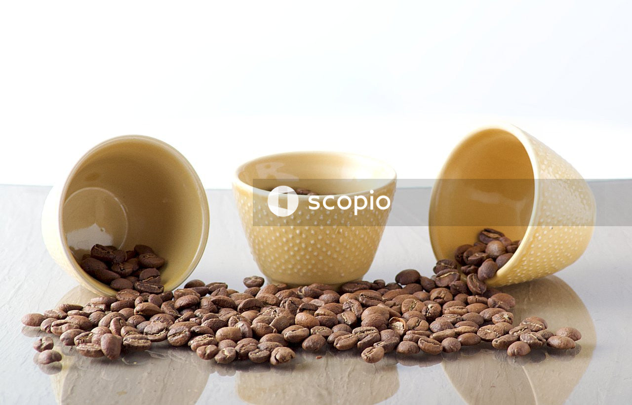 Brown coffee beans beside yellow ceramic mug