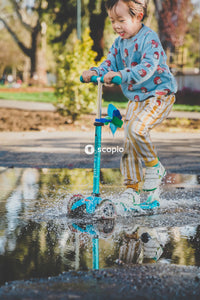 Boy riding push scooter across puddle