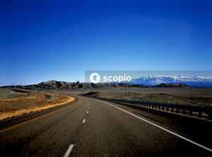 Black asphalt road under blue sky