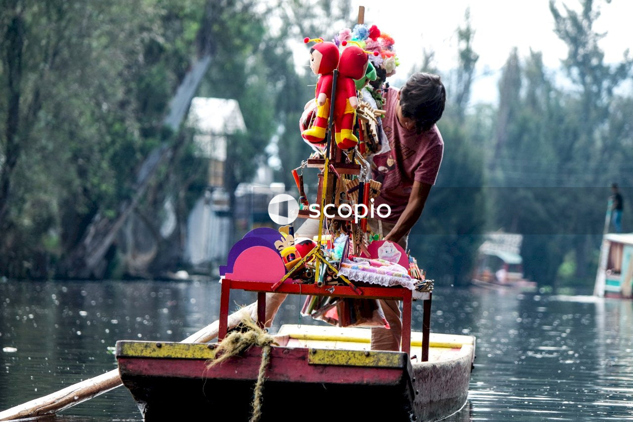 A boy rides in a boat with colorful articles aboard