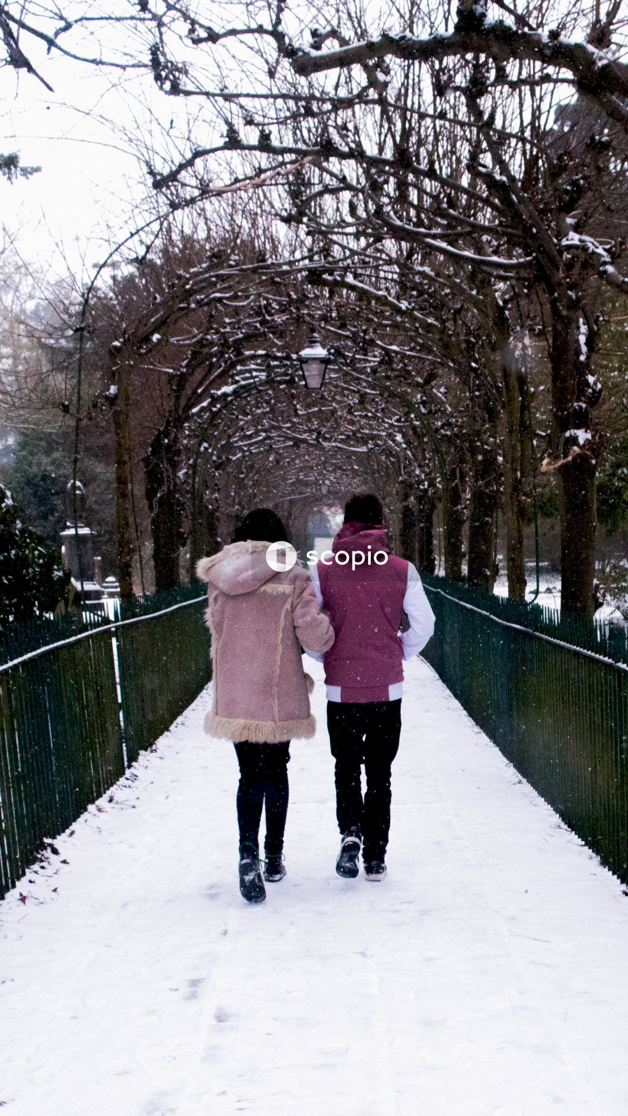 Woman in pink coat walking on snow covered pathway