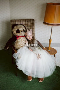 Young girl wearing white tutu and paper crown holding wand in her hand sitting on armchair next to panda stuffed bear