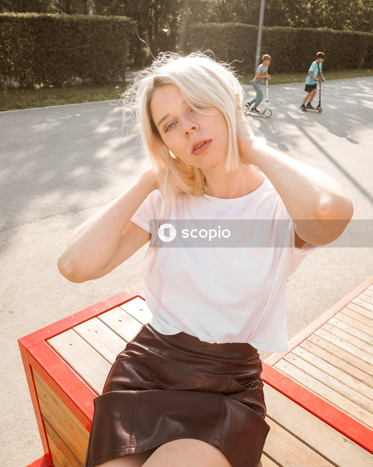 Girl in white tank top and black skirt sitting on red wooden bench
