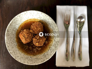 Food in bowl beside fork and spoon