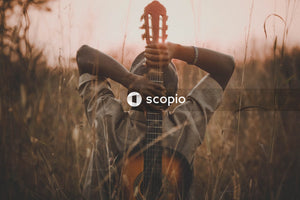 Man holding classical guitar while sitting on grass field during sunset
